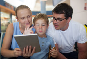 Family looking at a scrapbook page on a tablet
